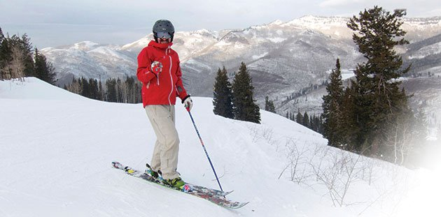Image of person in red jacket on skis and they are atop of a snowy mountain with more mountains in the back