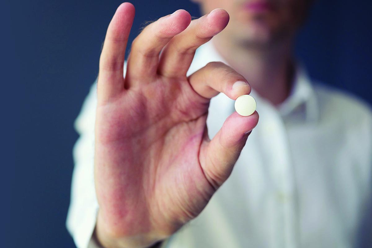 photo of man holding up an aspirin pill