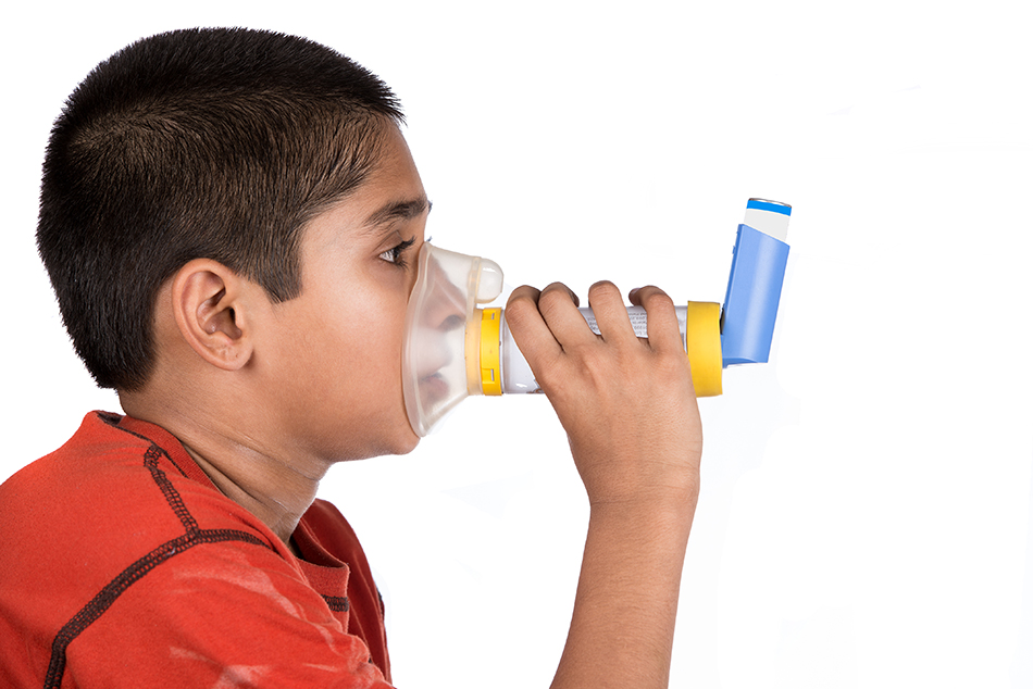 photo of young boy using a holding chamber and his asthma medication