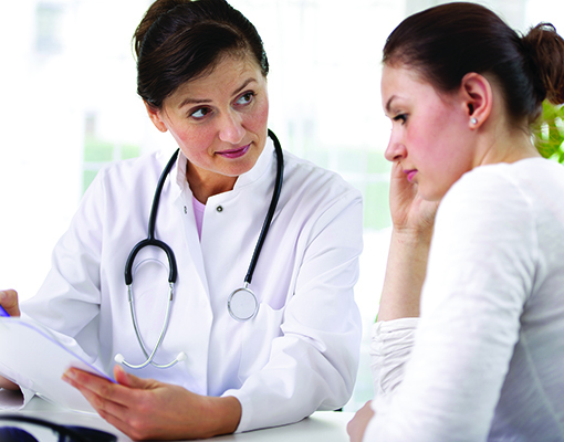 Photo of female doctor consulting with a young female patient