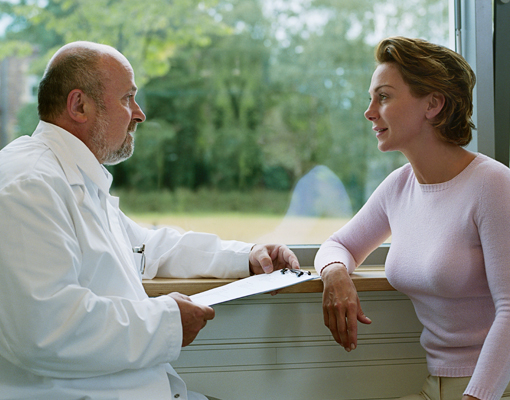 Photo of male doctor talking to female patient