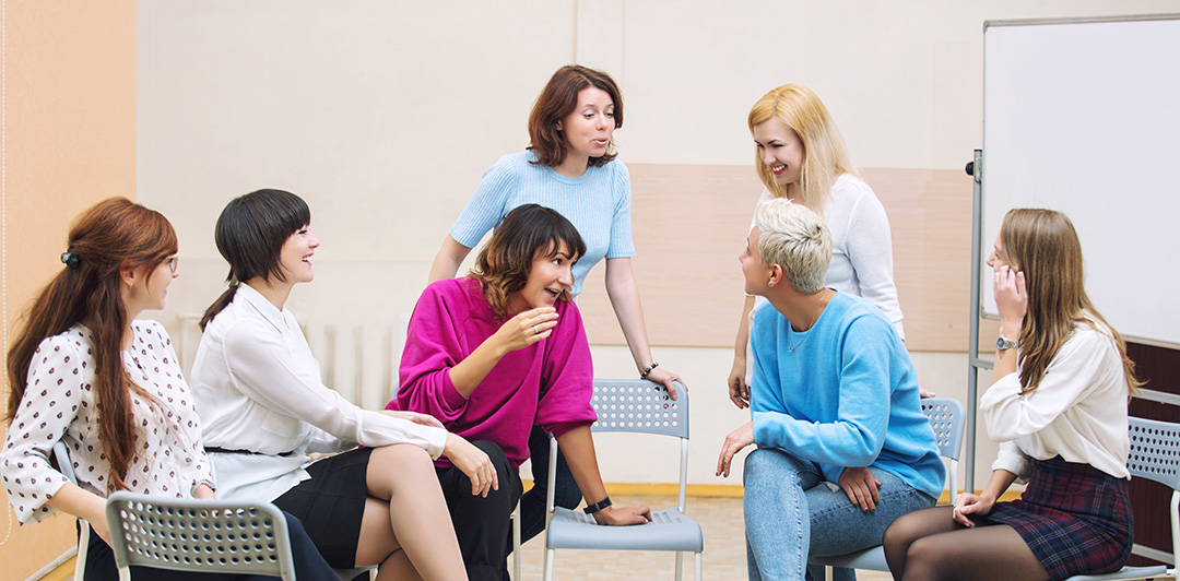 Photo of a group of women in a circle discussing a topic