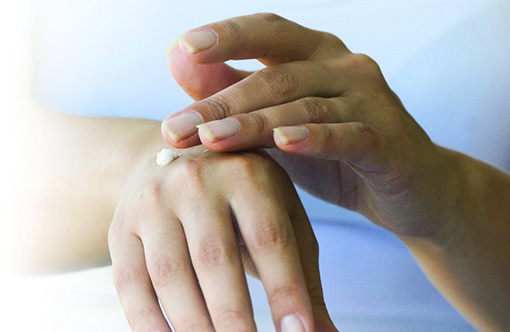 Photo of woman applying lotion to her hand
