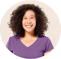 Image of mixed race Black and Asian woman wearing a purple shirt and a big smile