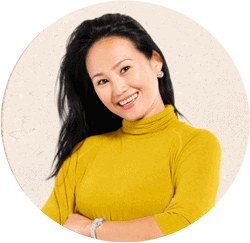 Portrait of young Asian woman smiling. She has long dark hair and is wearing a yellow sweater