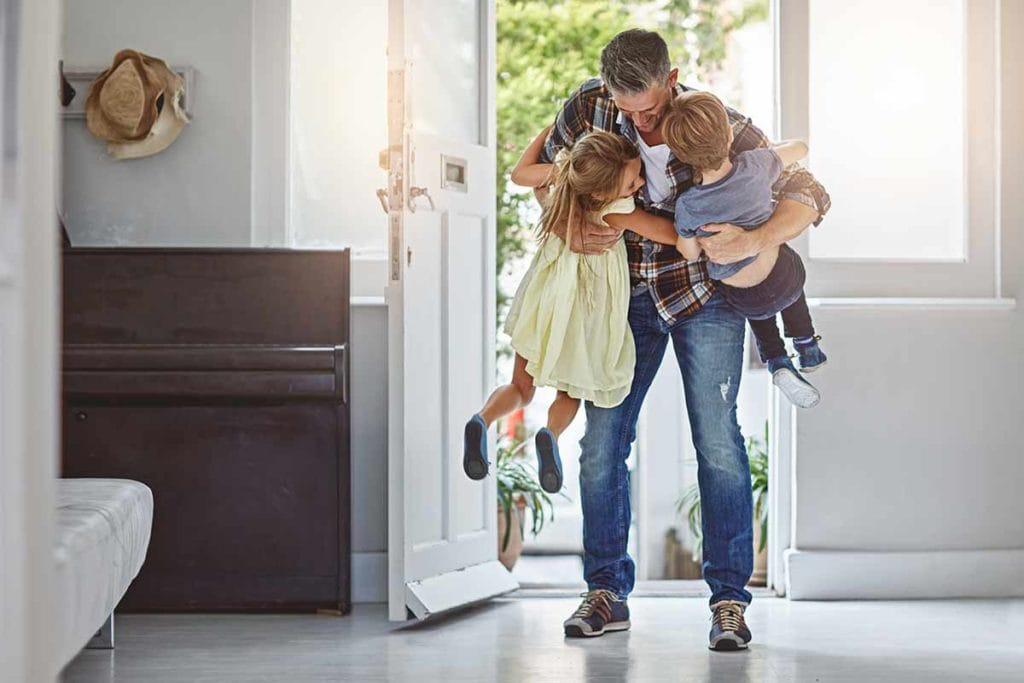 Image of father holding his kids up and hugging them at the same time. It appears as if he just came in the door and they ran up to him.
