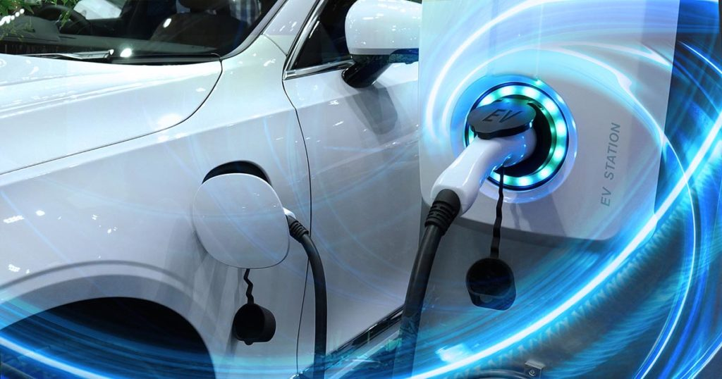 Photo of EV Car or Electric vehicle at charging station with the power cable supply plugged in on blurred nature with blue enegy power effect. Eco-friendly sustainable energy concept.