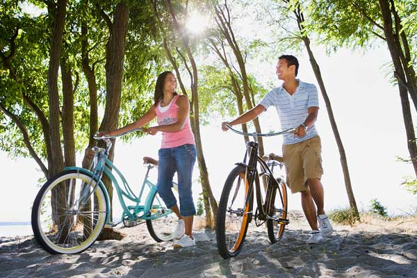Couple with bicycles in the park. They're under the trees, away from the summer sun.