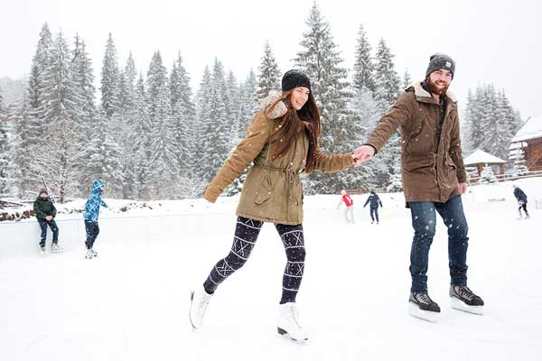 People at an outdoor skating rink. The foreground has a young couple holding hands.
