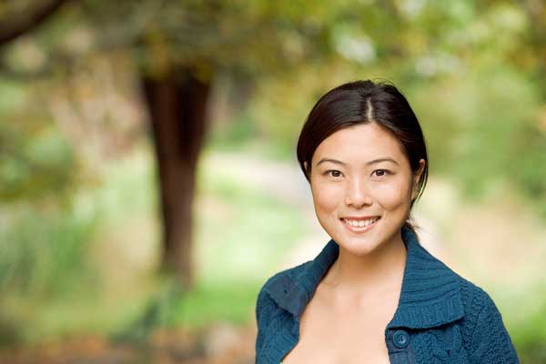 Young Asian woman smiling while facing the camera. She's in the park during a lovely spring day.