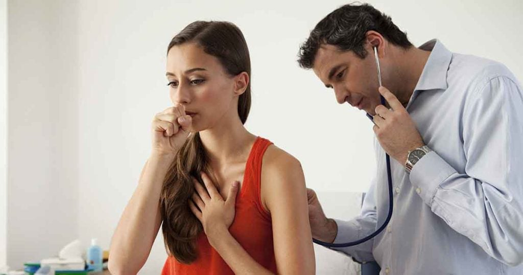 Photo of a woman coughing with a male doctor listening to her lungs