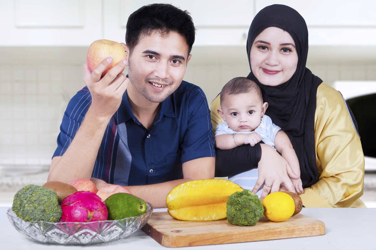 Portrait of healthy asian family smiling at the camera while sitting in the kitchen with fresh fruits