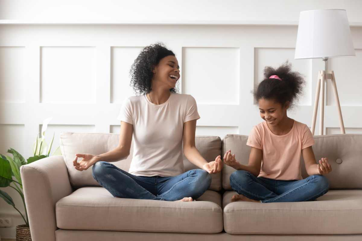 Mixed-race mother little daughter distracted from meditation laughing sit in lotus position on couch in living room, mom teach kid beginner yoga asana, healthy life habits, activities at home