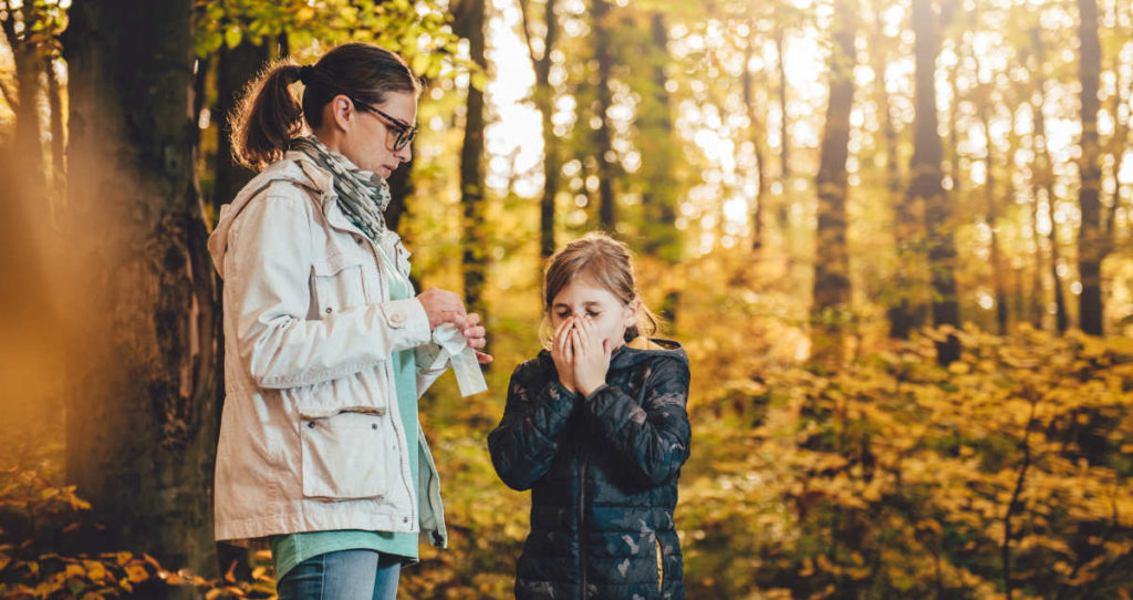 Child is sneezing from the hay fever pollen in the park. Her mother is standing next to her holding a tissue, waiting to hand it to her. It appears to be the autumn season.