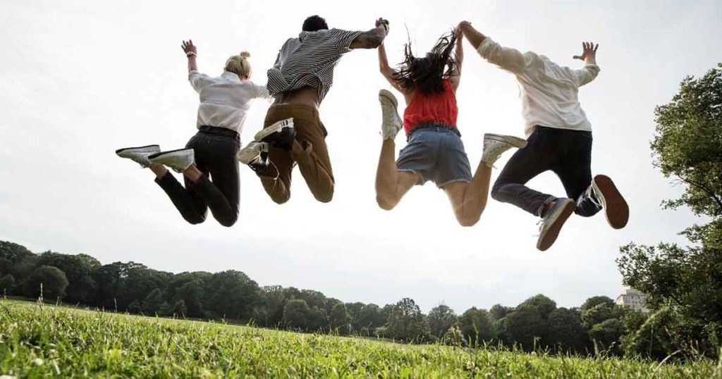Photo of four people jumping in the air in a field