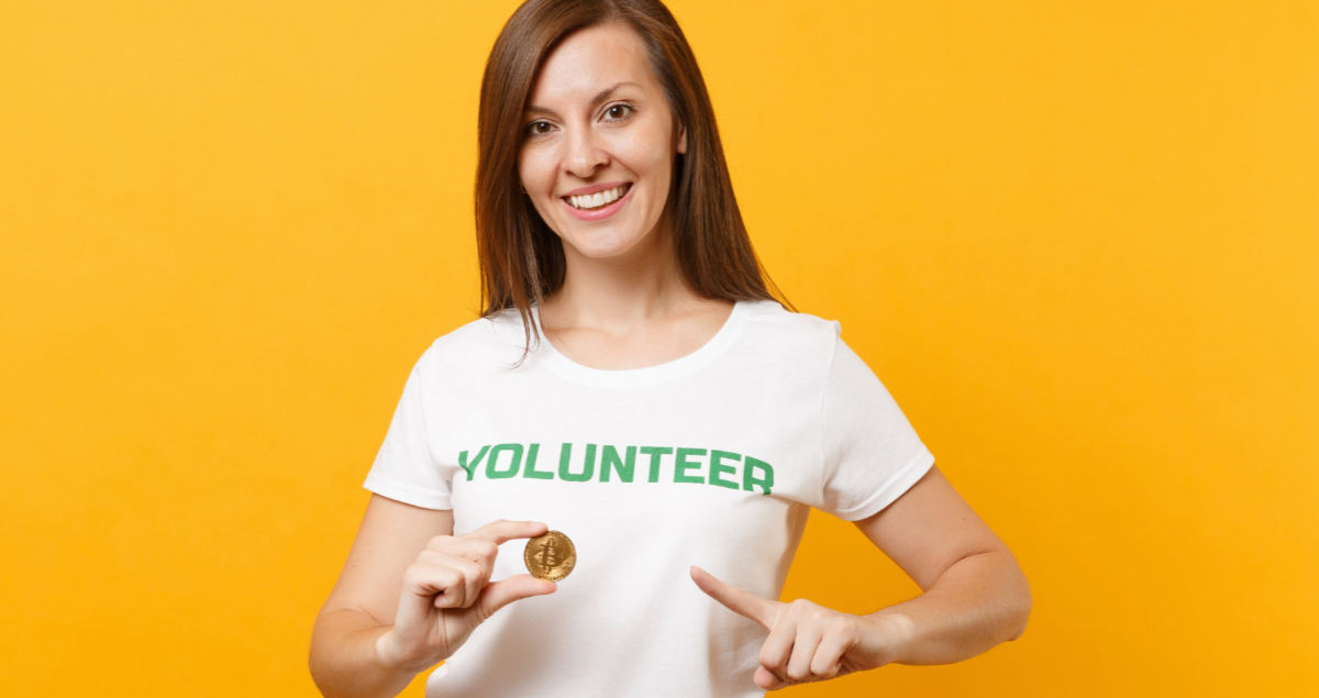 """Woman in white Tshirt with the word """"volunteer"""" on it is holding up a bitcoin coin and pointing to it with her other hand. The concept is the organization accepts cryptocurrency donations including Bitcoin."""