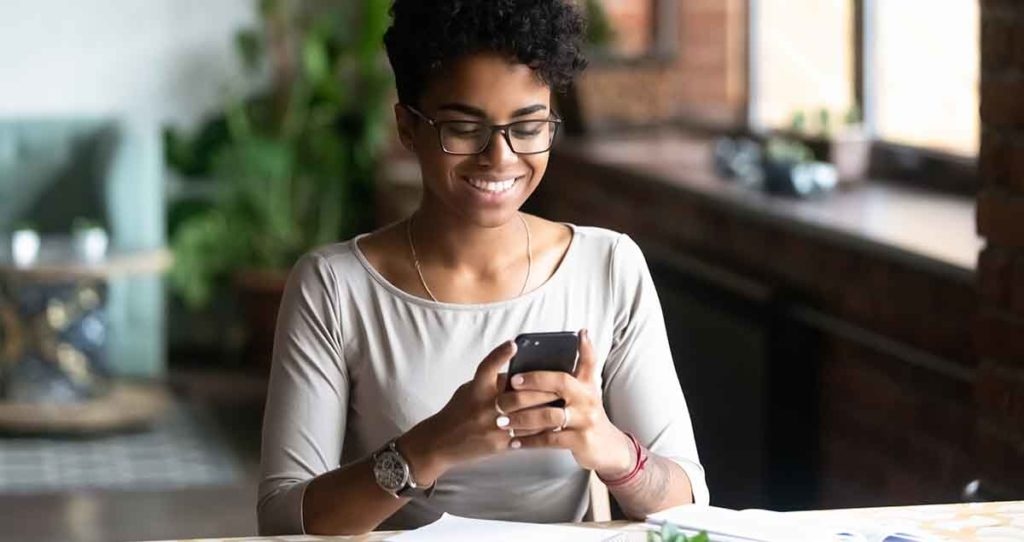 Photo of black woman using her smart phone at the kitchen counter