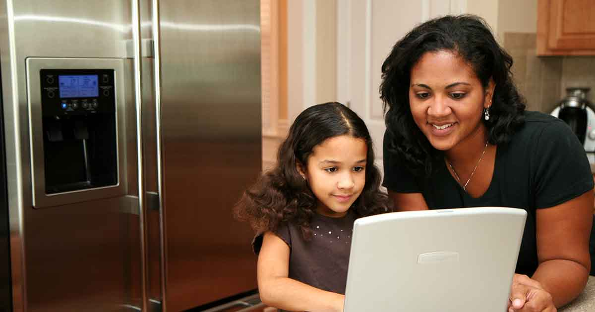 Photo of Woman in her kitchen with daughter on the computer